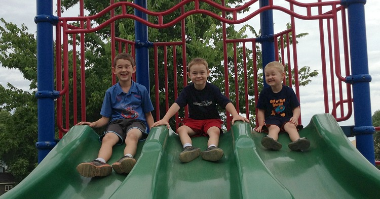 three boys on slide